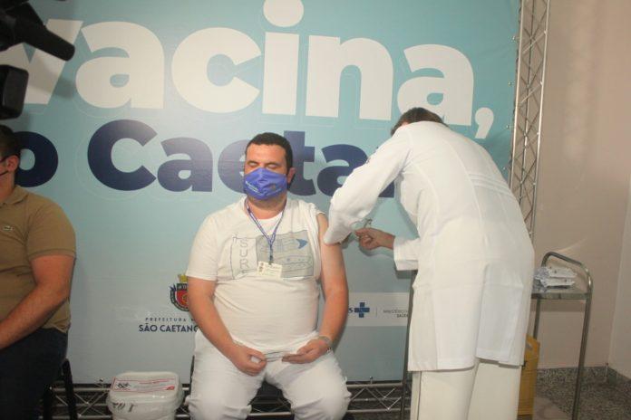 A Secretária de Saúde de São Caetano, Regina Maura Zetone aplica a segunda dose no enfermeiro Felipe Maciel que está na linha de frente.